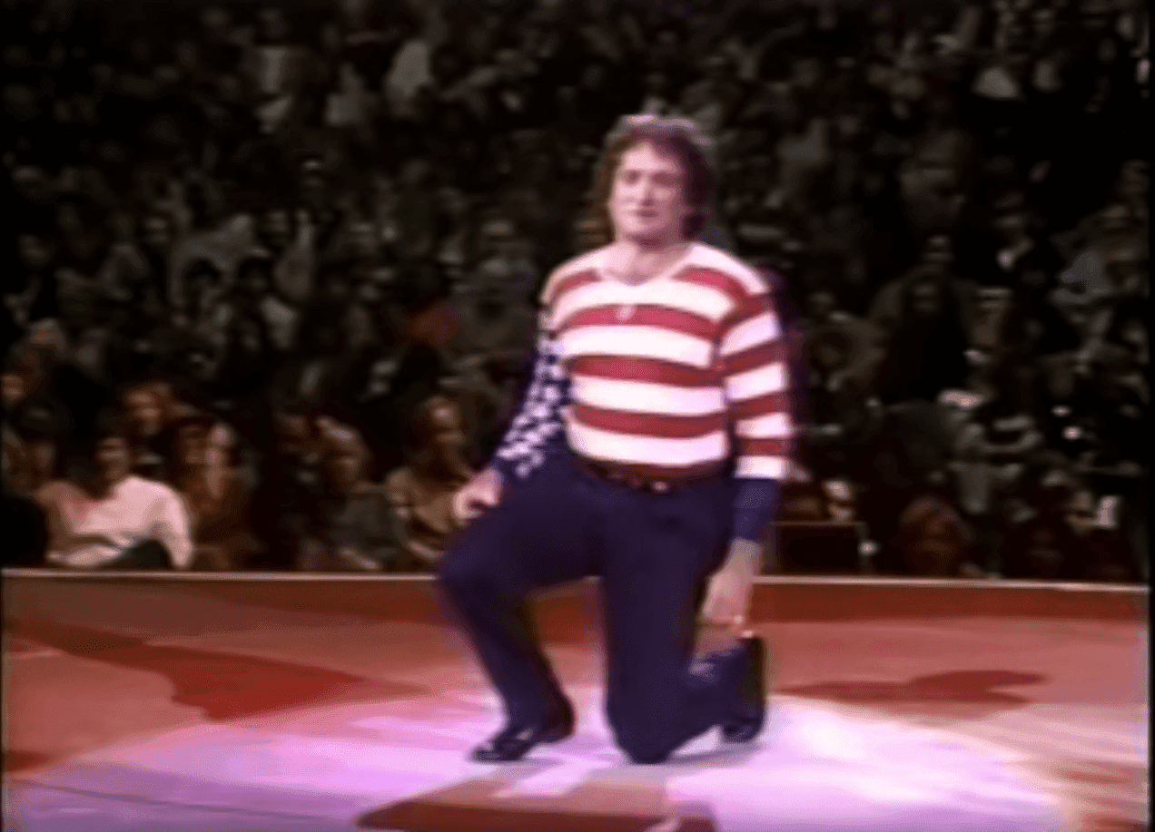 Robin Williams kneeling during the performance. l Image: YouTube/ PAFWdotorg.