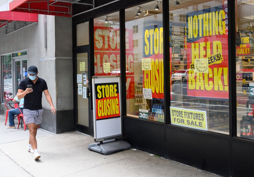 """A person wears a protective face mask outside a store that puts out the """"closing"""" sign on August 7, 2020 in New York City   Photo: Getty Images"""