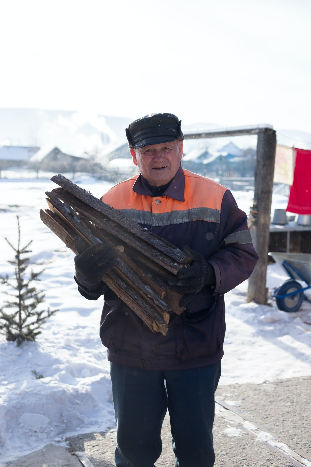 Old man carrying chopped wood   Photo: Pexels