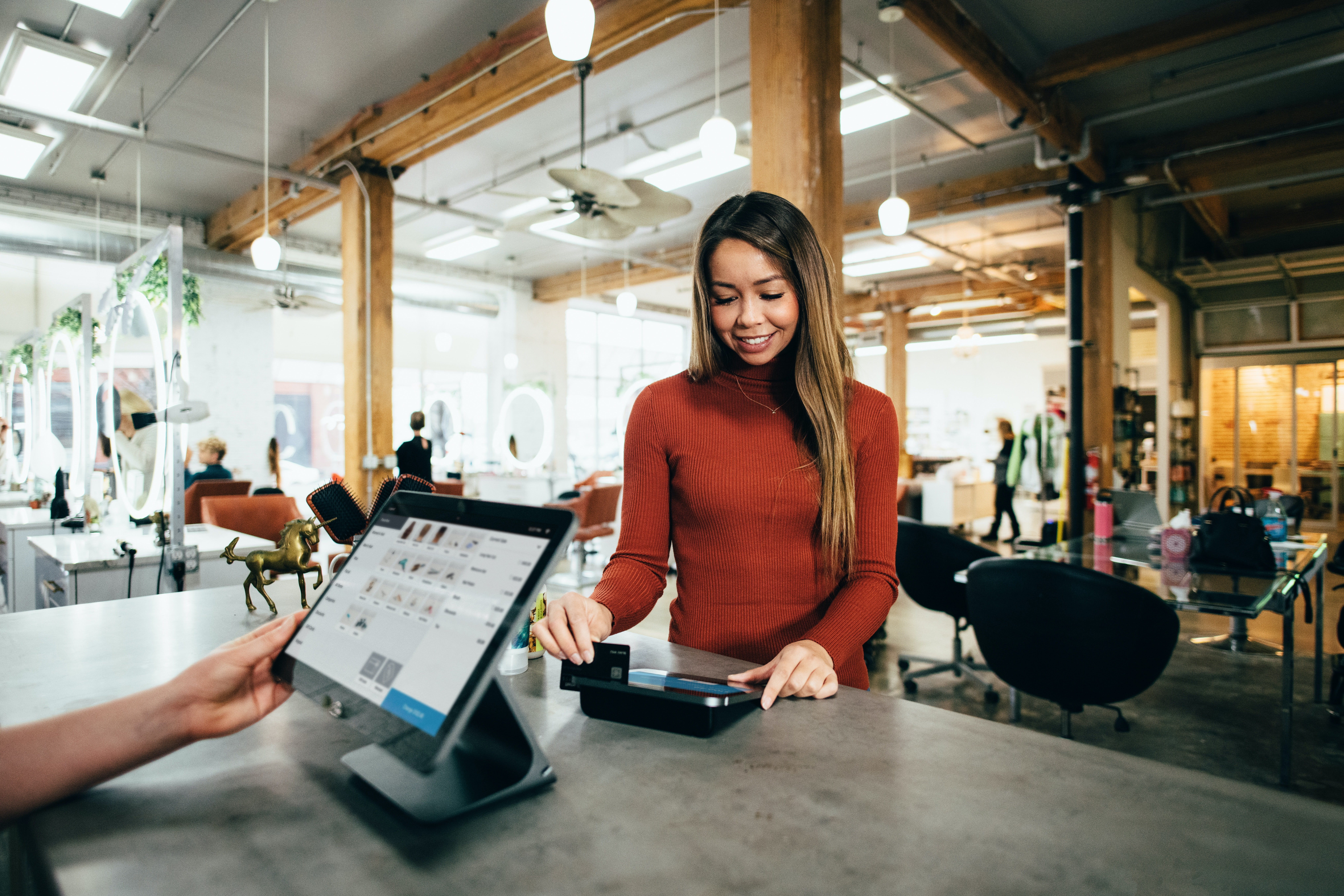 Woman paying at a store check out   Photo: Unsplash