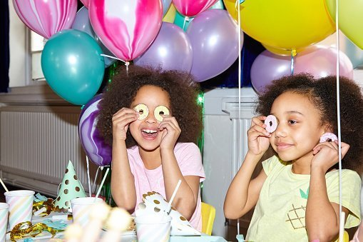 Young girl looking to camera having fun playing with food at a birthday celebration | Photo: Getty Images
