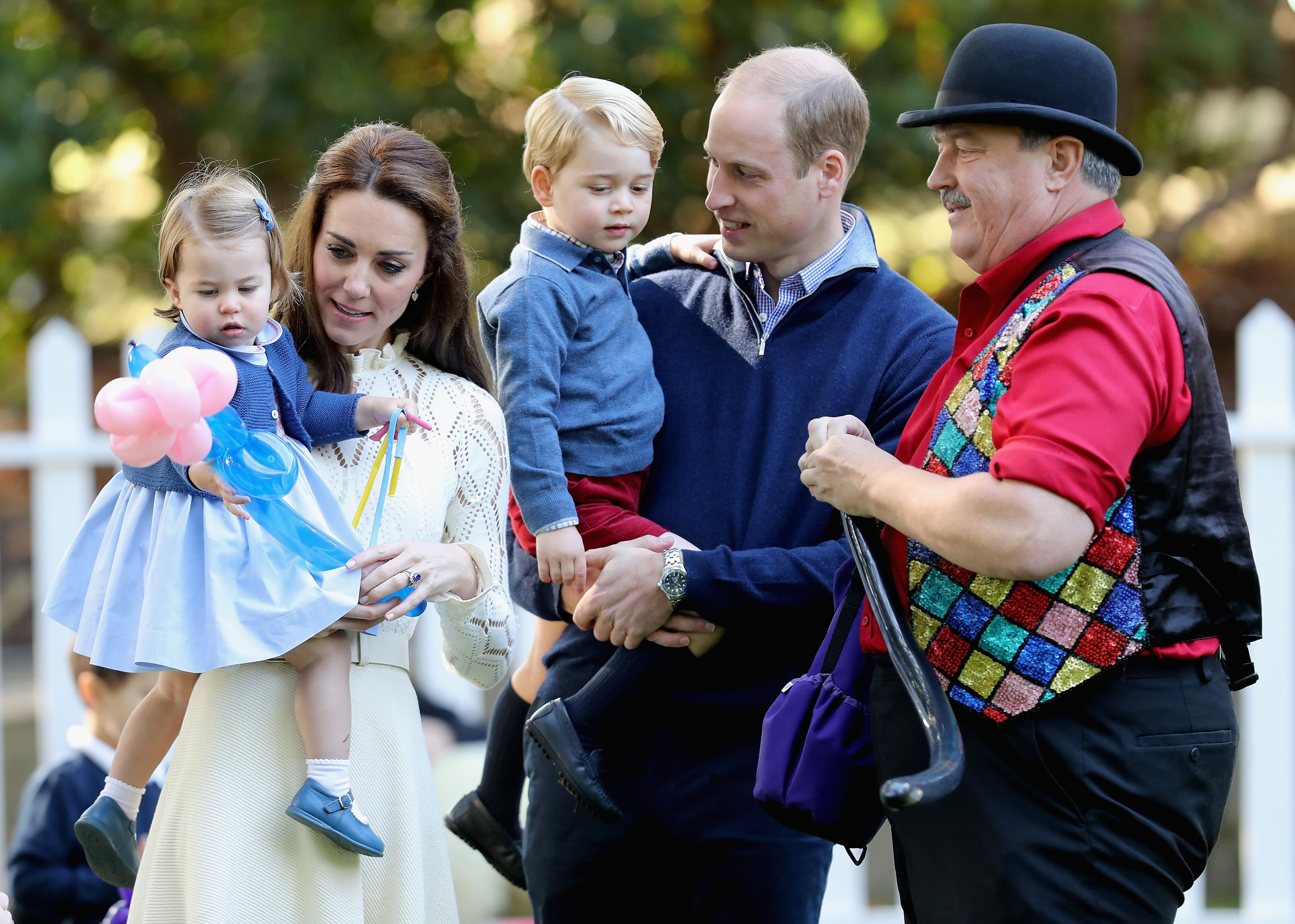 Duchess of Cambridge holding Princess Charlotte of Cambridge and Prince George of Cambridge, being held by Prince William, Duke of Cambridge at a children's party for Military families during the Royal Tour of Canada on September 29, 2016 in Victoria, Canada | Photo: Getty Images