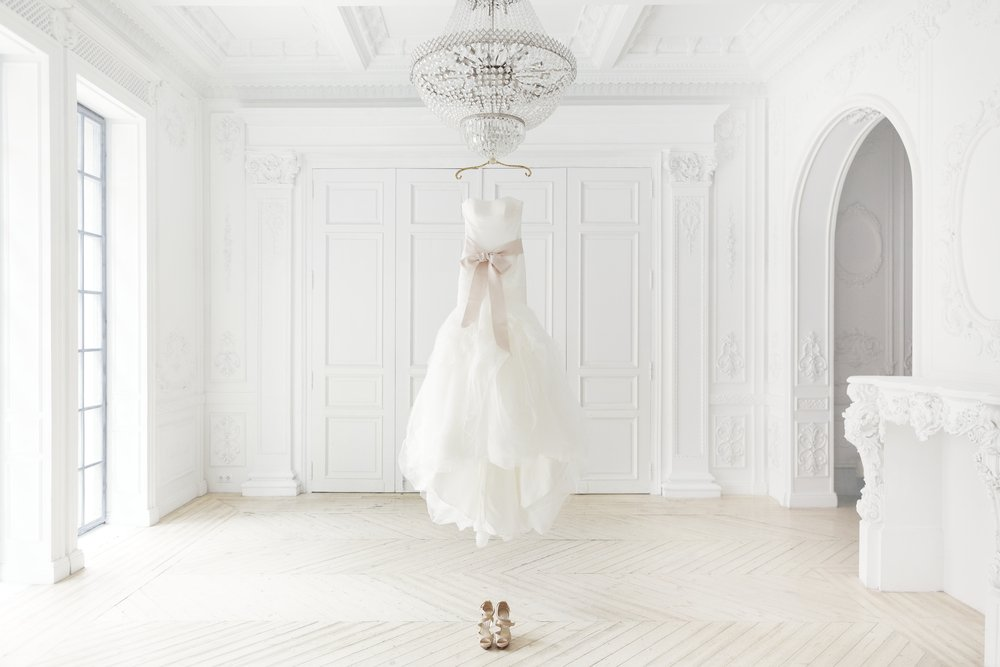 A white wedding dress hanging from the chandelier |Photo: Shutterstock