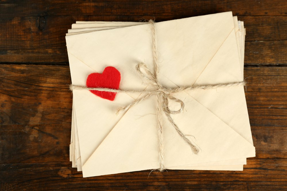 A stack of love letters on a wooden background. | Photo: Shutterstock