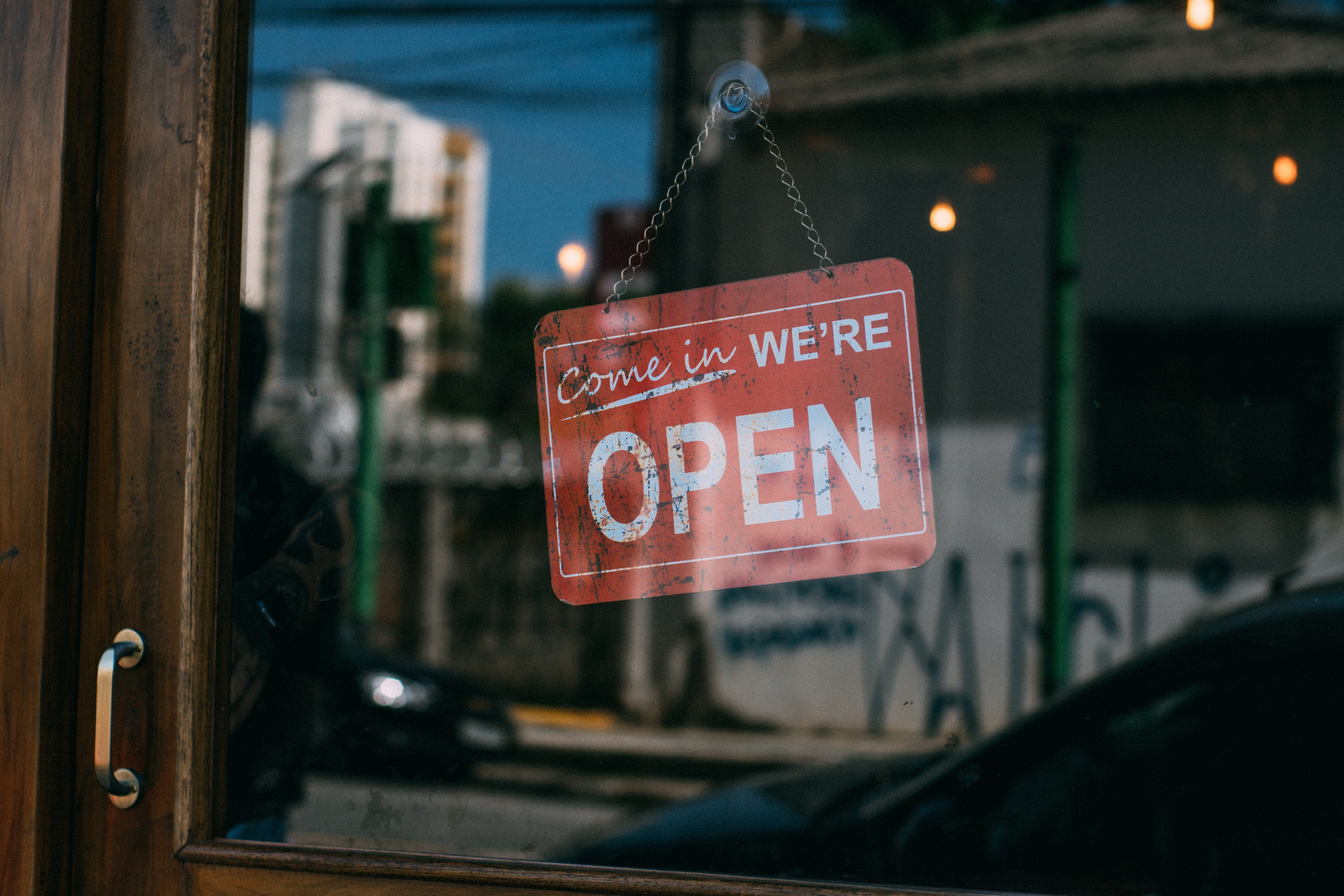 """A """"we're open"""" sign on the door of a store. 