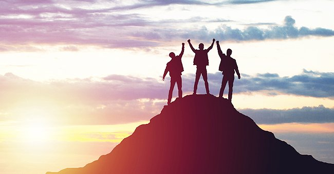 Three friends holding hands on a hill | Photo: Shutterstock