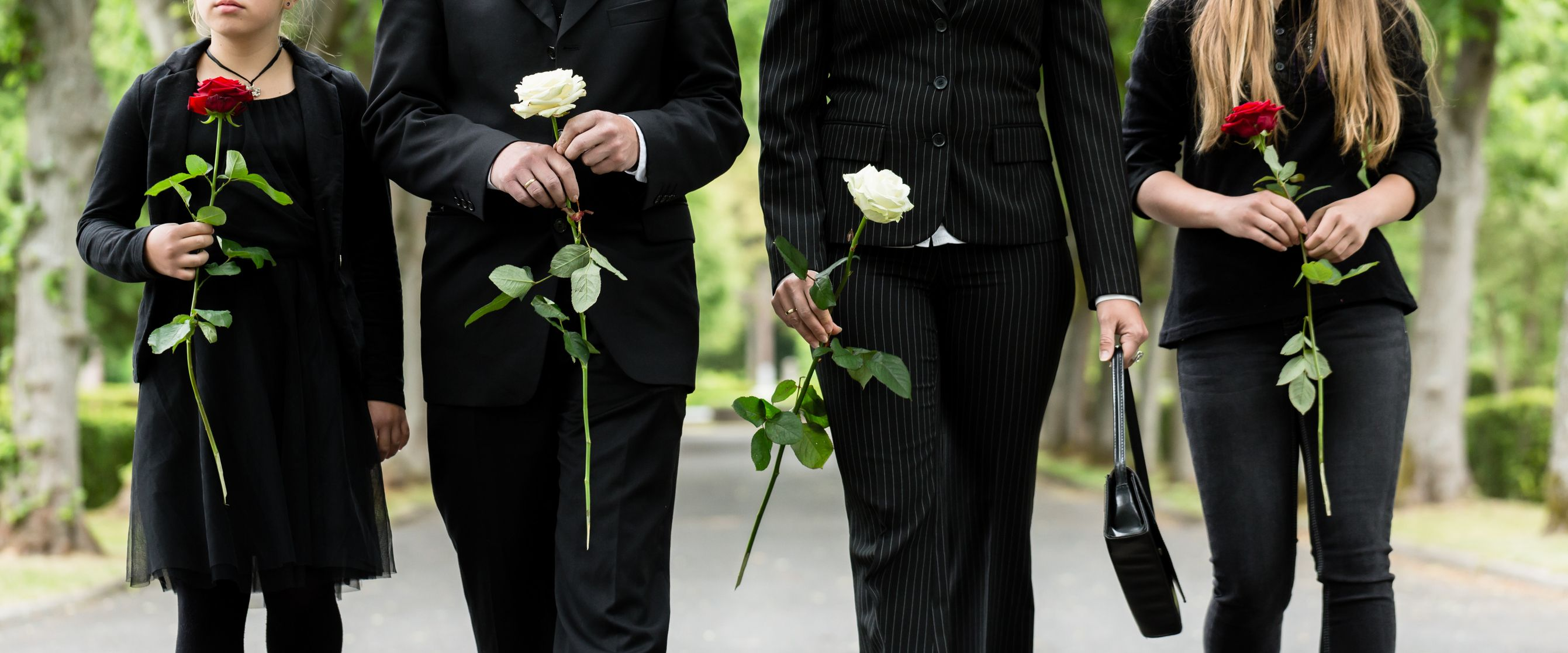 Midsection Of Family Holding Roses On Road During Funeral. | Quelle: Stock-Fotografie