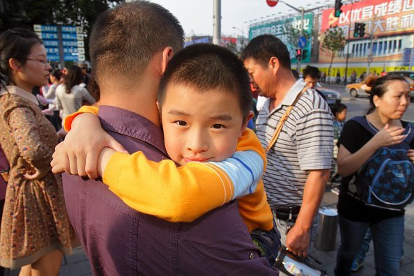 A young child with his father  on National Day Golden Week | Photo: Getty Images