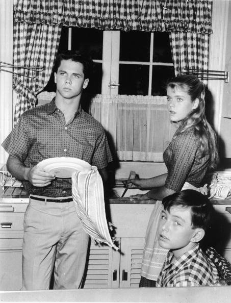 Tony Dow washes dishes with a towel as he stands in the kitchen alongside an unidentified actress and Jerry Matherswho sits and gives the camera a glance, circa 1960. | Source: Getty Images.