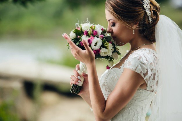 Bride enjoying the scent of her bouquet. | Photo: Freepik