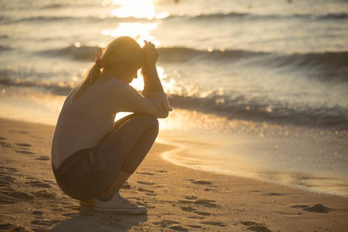A worried young woman sitting by the water's edge. | Source: Shutterstock.