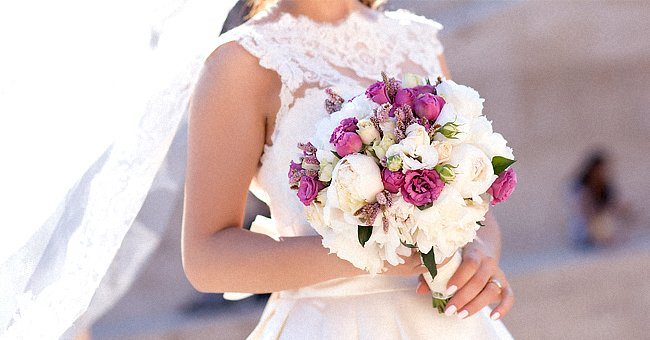 A bride dressed in her white dress holds a bouquet of flowers | Photo: Shutterstock