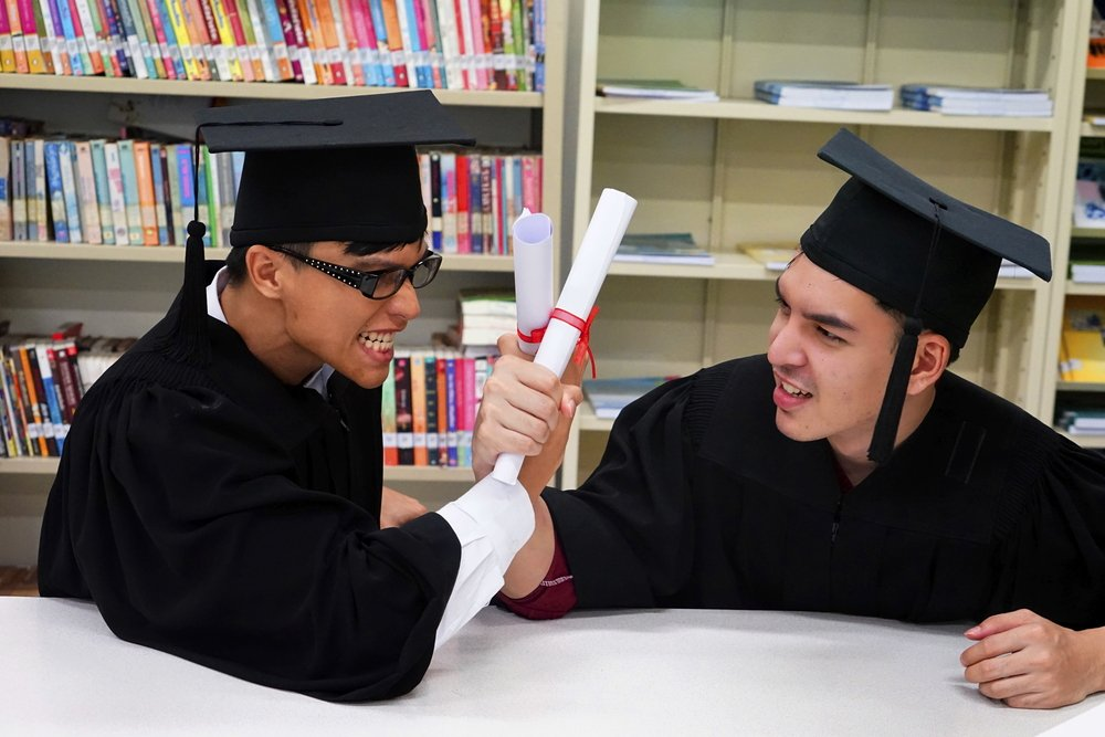 Two law graduates with gown happy in the library. | Photo: Shutterstock