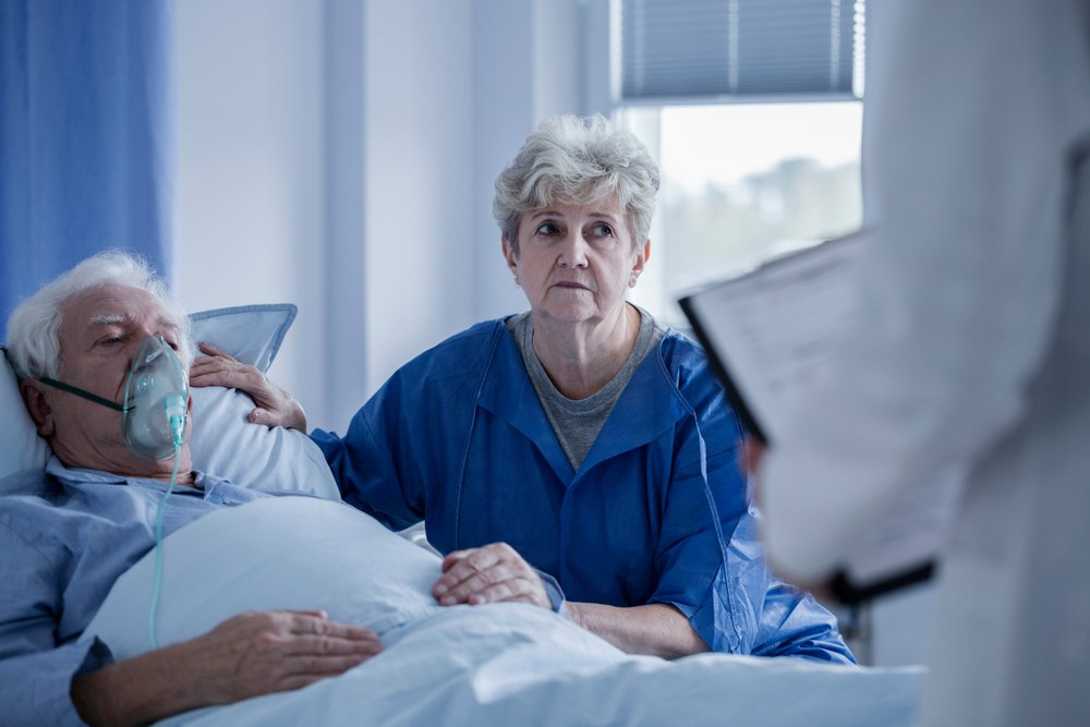 Photo of a woman by her husband's side in the hospital. | Photo: Shutterstock.
