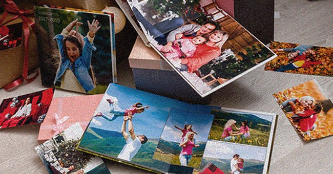 A photo album lies on a table a features multiple family pictures | Photo: Shutterstock