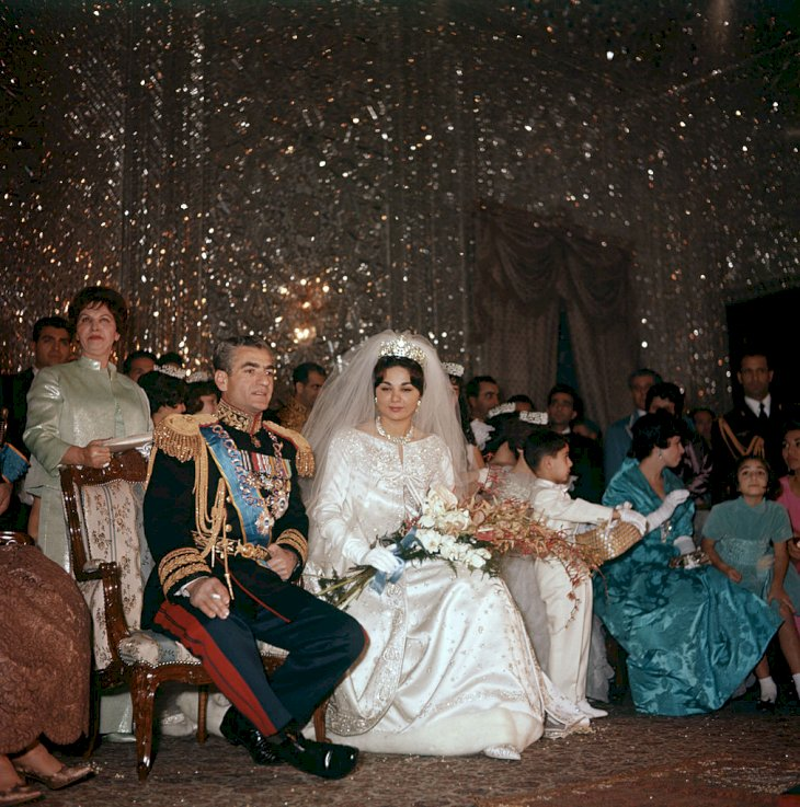 Mohammad Reza Pahlavi, Shah of Iran, is seated next to her third wife Farah Diba on the day of their marriage; her gown is by Yves St Laurent and on her head a Noor-ol-Ain Diamond tiara. Iran, 21st December 1959. (Photo by Mondadori Portfolio by Getty Images)