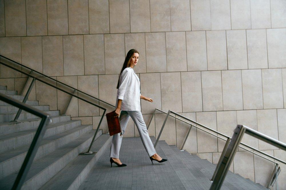 Mujer sonriente en ropa de oficina elegante bajando las escaleras. | Fuente: Shutterstock