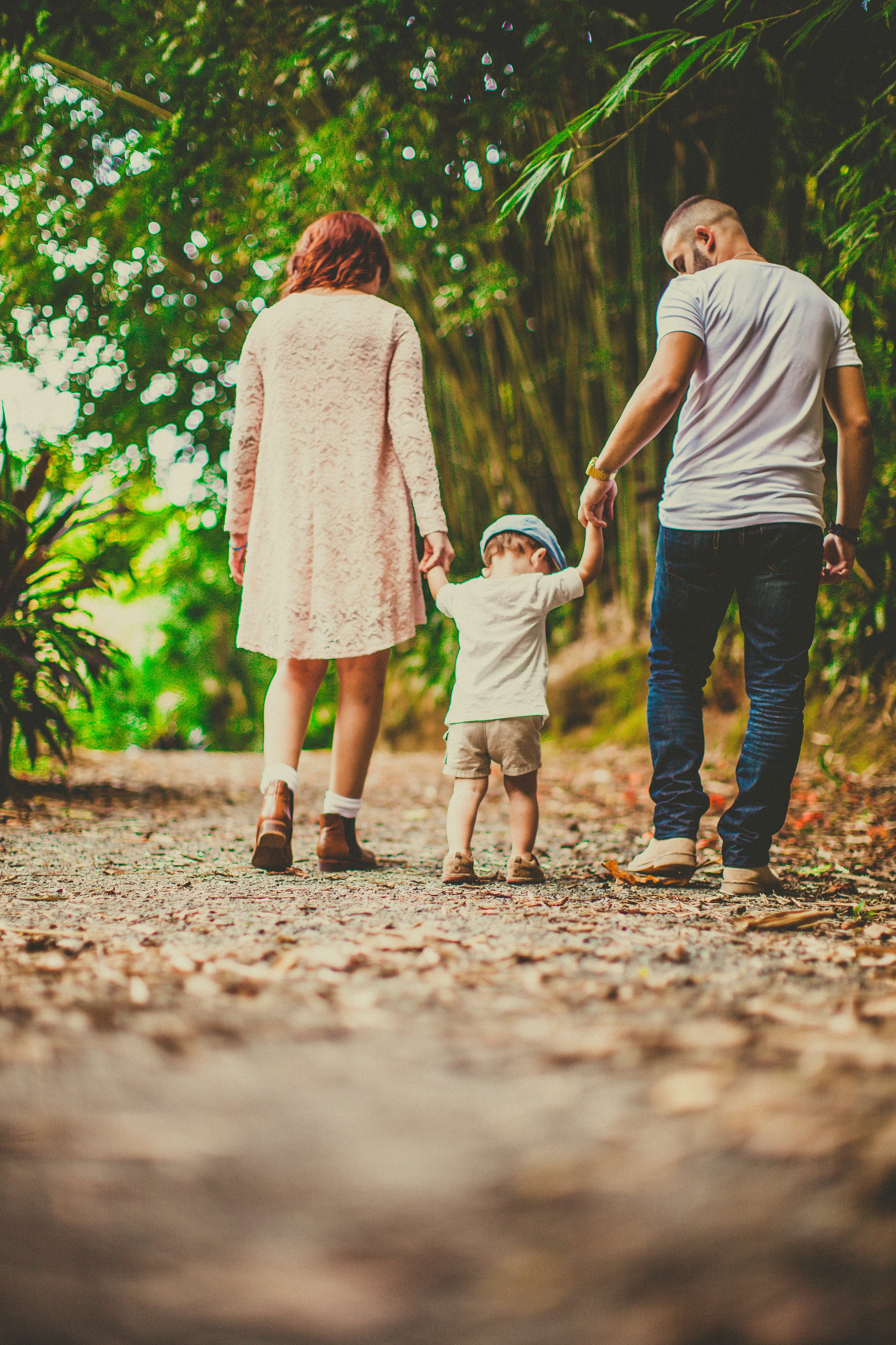 A couple with their son holding his hands on each side walking in an unpaved pathway outdoors   Source: Pexels