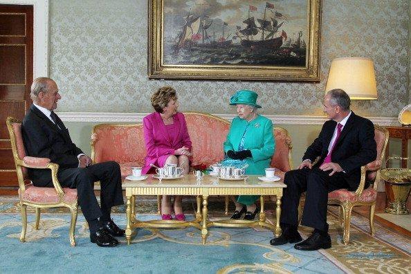 Le prince Philip le duc d'Édimbourg, la présidente Mary Mc Aleese, la reine Elizabeth II et le Dr Martin Mc Aleese s'entretiennent autour d'une tasse de thé à Aras An Uachtarain à Dublin, Irlande. | Photo : Getty Images