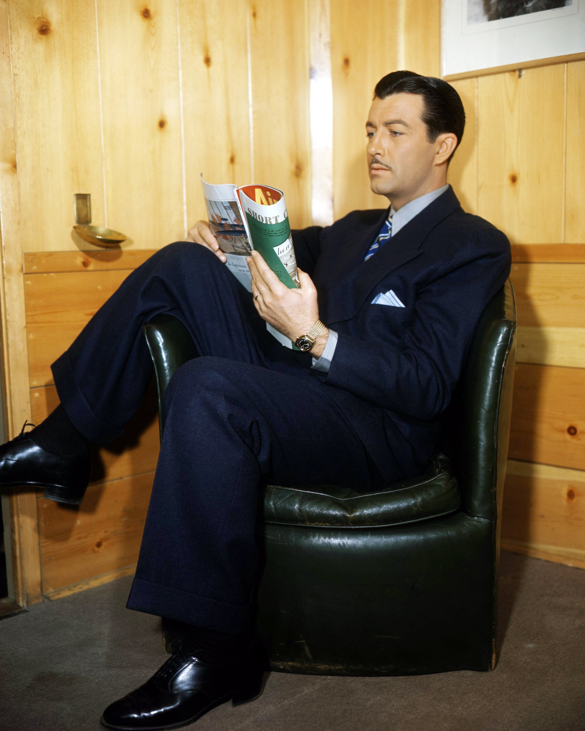 American actor Robert Taylor (1911 - 1969) sitting in an armchair and reading a magazine, circa 1940. | Source: Getty Images