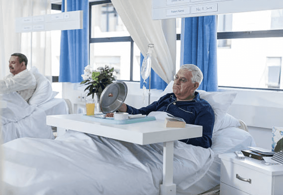 Senior patient looking at his meal in hospital bed | Source: Getty Images
