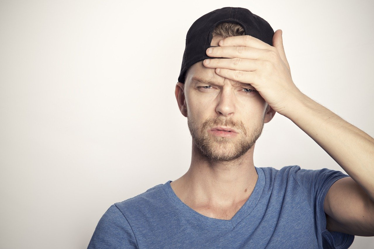 A man holding his forehead with a confused look on his face   Photo: Pixabay/Sammy-Williams
