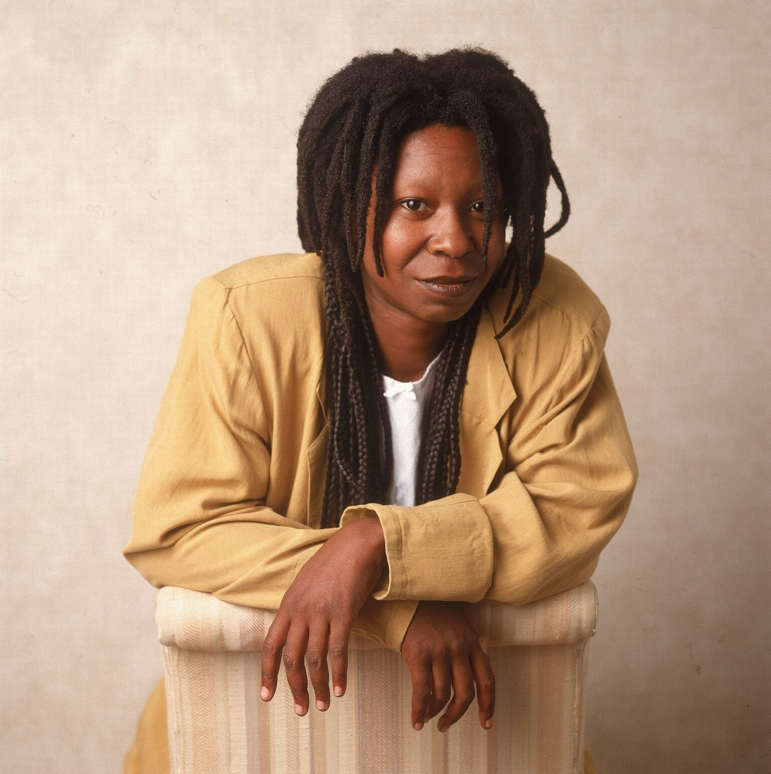 American actor and comedian Whoopi Goldberg leaning on a chair, 1988 | Getty Images