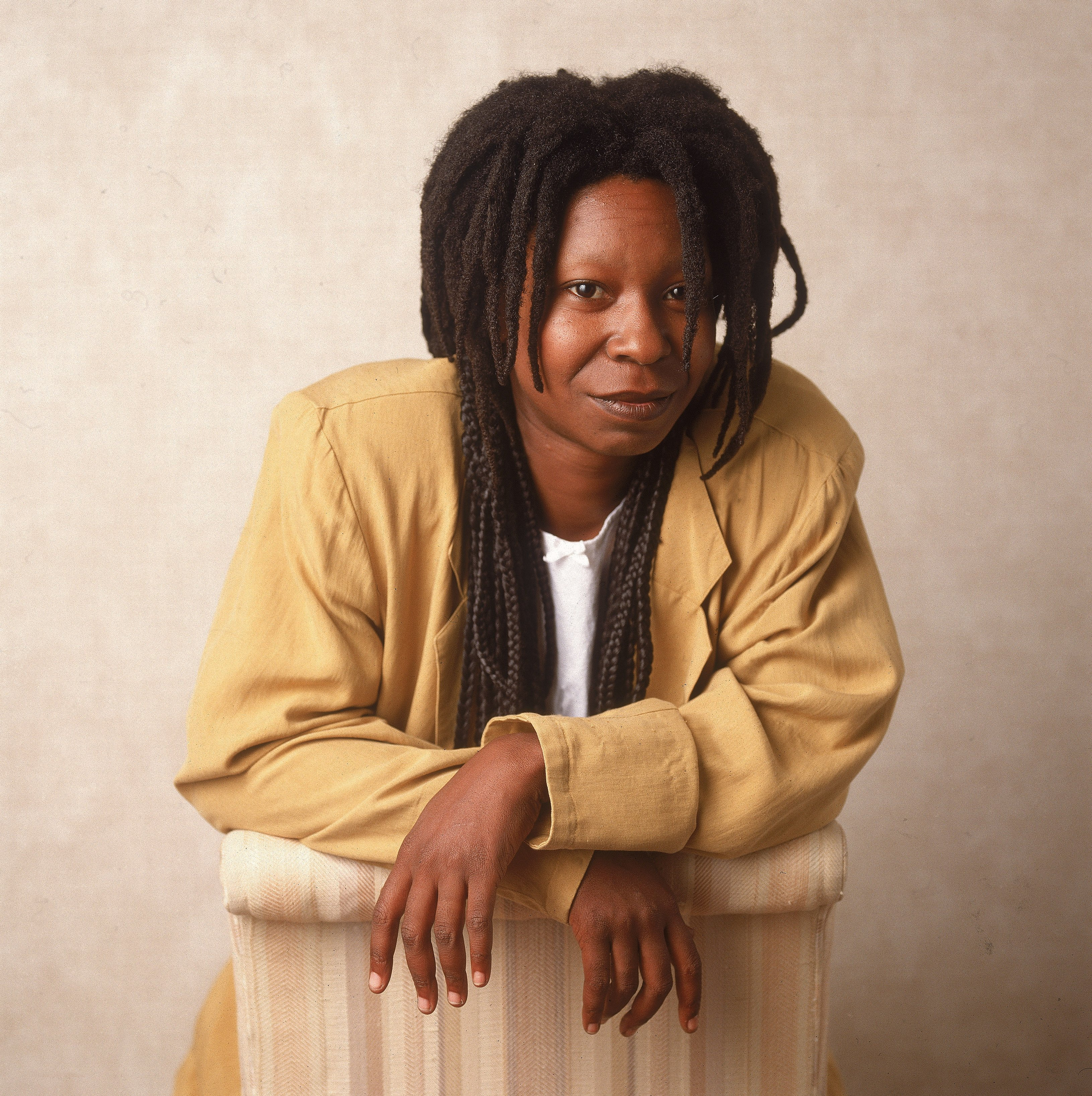 Studio portrait of American actor and comedian Whoopi Goldberg leaning on a chair, 1988. | Source: Getty Images