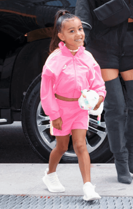 North West smiles in a pink neon outfit as paparazzi spot her on a ice cream date with Kim Kardashian, on June 14, 2018, New York City | Source: Gotham/GC Images