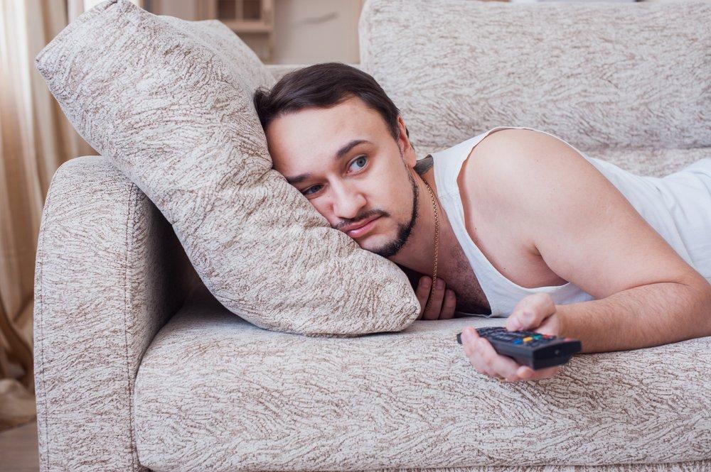 Un homme face contre terre sur un canapé changeant de chaîne de télévision. | Source : Shutterstock