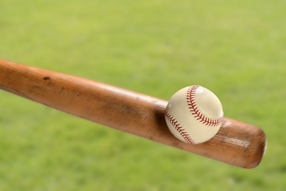 Baseball bat hitting ball over grass | Photo: Shutterstock