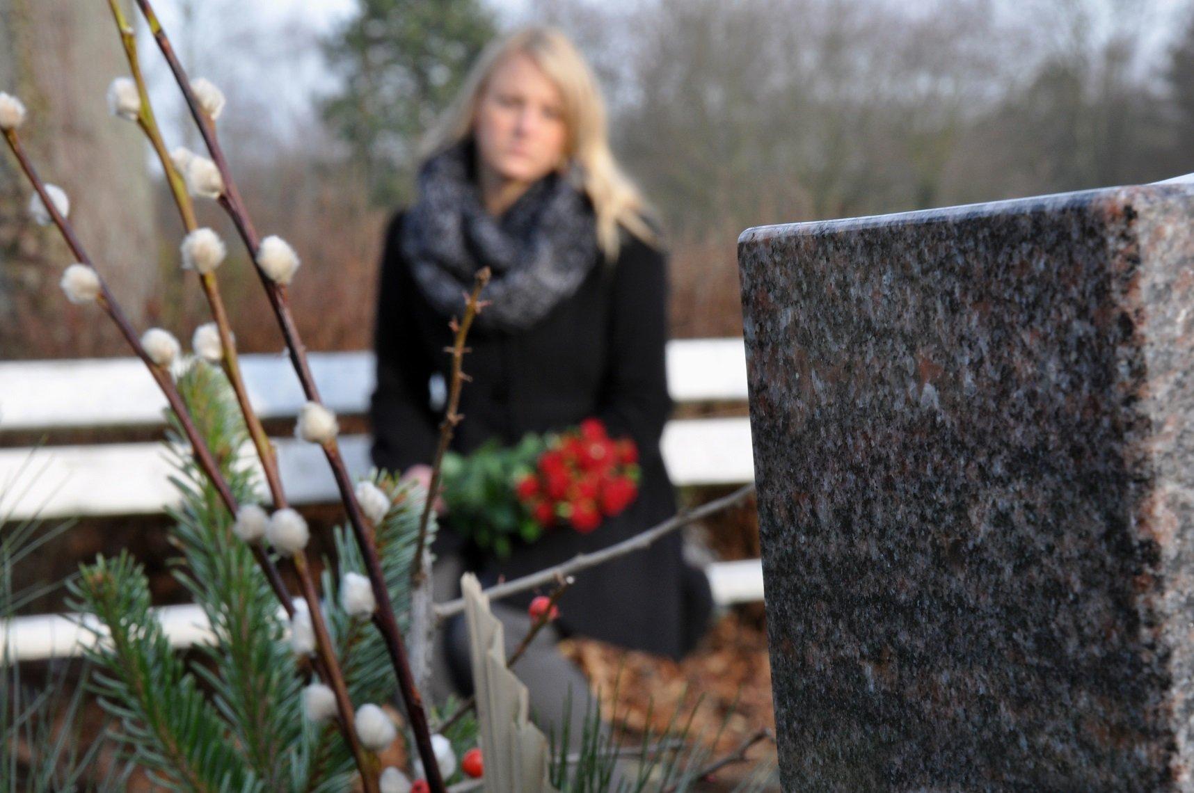 Mujer visita tumba en cementerio || Fuente: Shutterstock