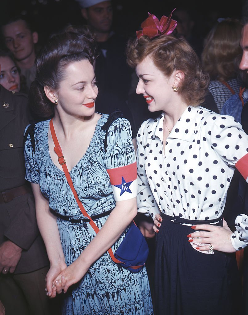Joan Fontaine and Olivia de Havilland smile at each other as they attend an event at the Hollywood Canteen, Los Angeles, California on January 1,1940. | Photo: Getty Images.
