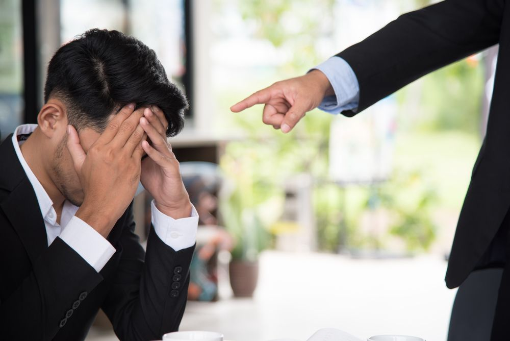 A man in a suit, sitting on the floor, while another man points at him. | Source: Shutterstock