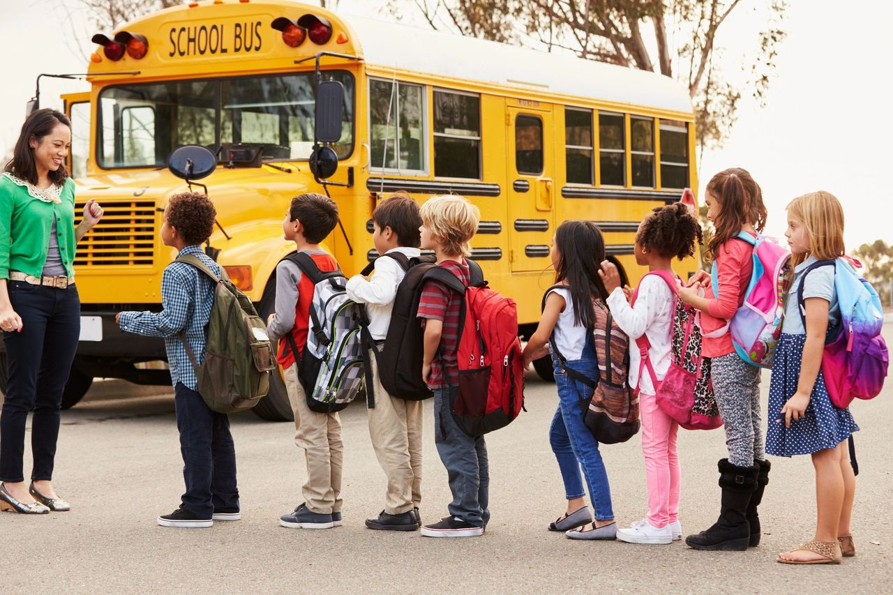 Elementary school students line up before a school bus.   Source: Shutterstock