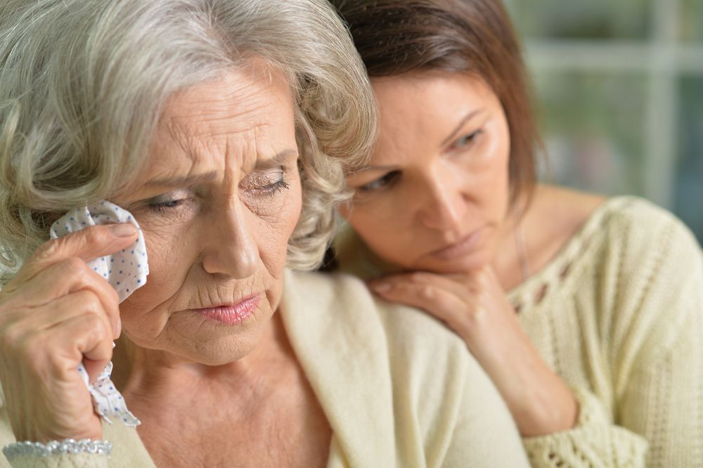An old woman and a young woman sitting beside each other.   Source: Shutterstock