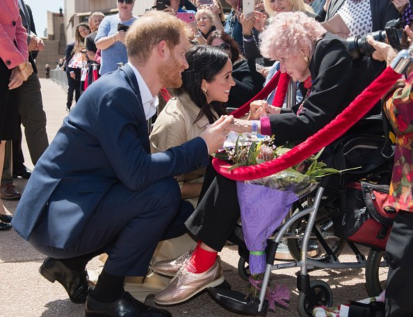 Prince Harry and Meghan with Daphne Dunne at the Sydney Opera House in Sydney, Australia. | Photo: Getty Images.