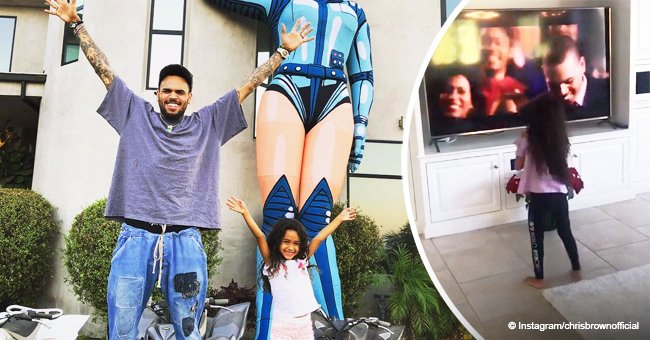 Chris Brown's daughter gets excited while watching her dad perform in a movie on TV