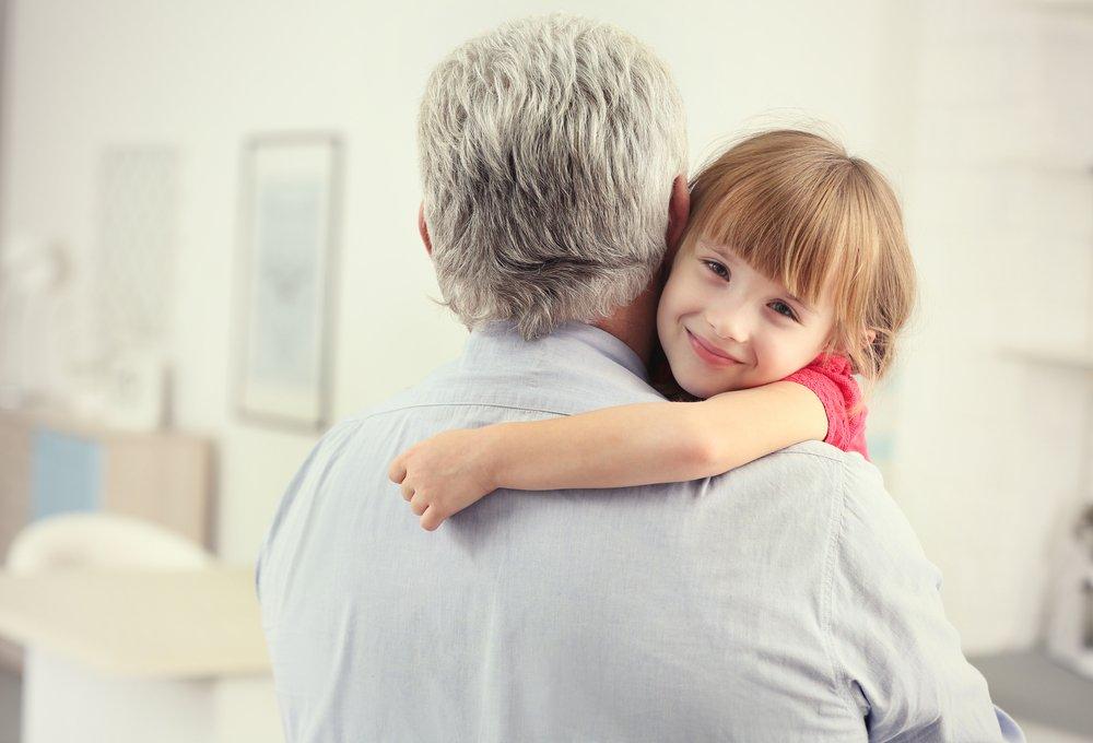Niña abrazando a su abuelo en casa. | Fuente: Shutterstock