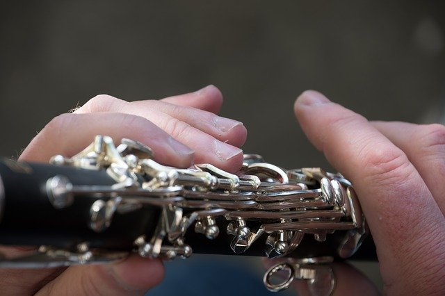 Close up photograph of the hands of a man playing a clarinet. I Image: Pixabay.