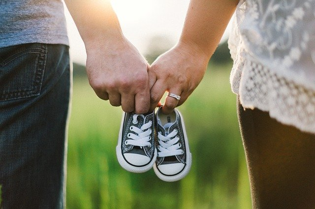 Couple walking together holding baby shoes   Source: Pixabay