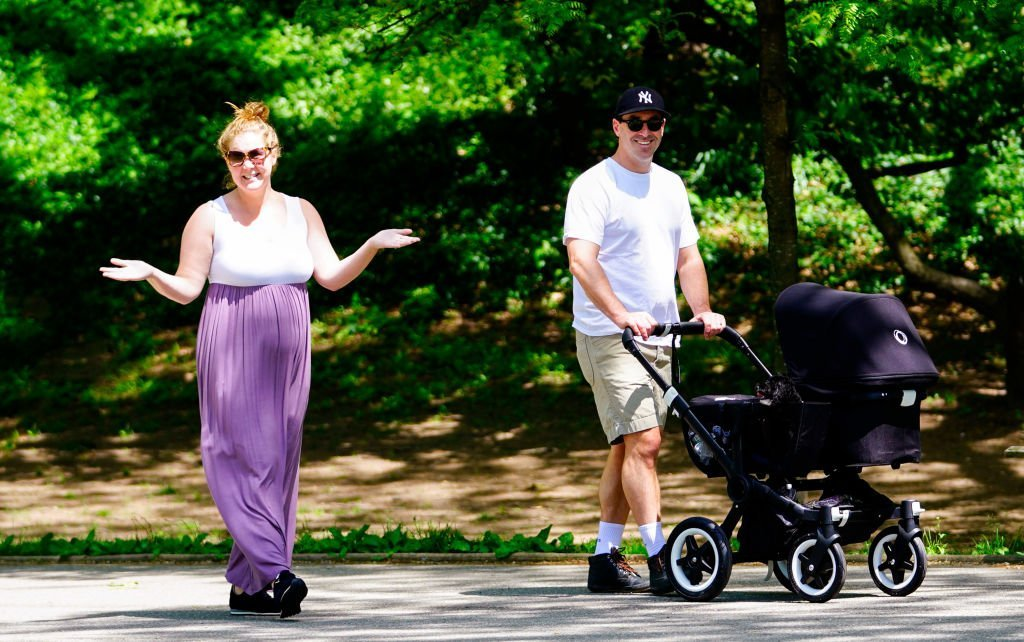 Amy Schumer and Chris Fischer take baby Gene Attell Fischer and their dog to the park on May 18, 2019. | Photo: Getty Images