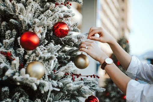 Woman decorating and hanging baubles on Christmas tree | Photo: Getty Images