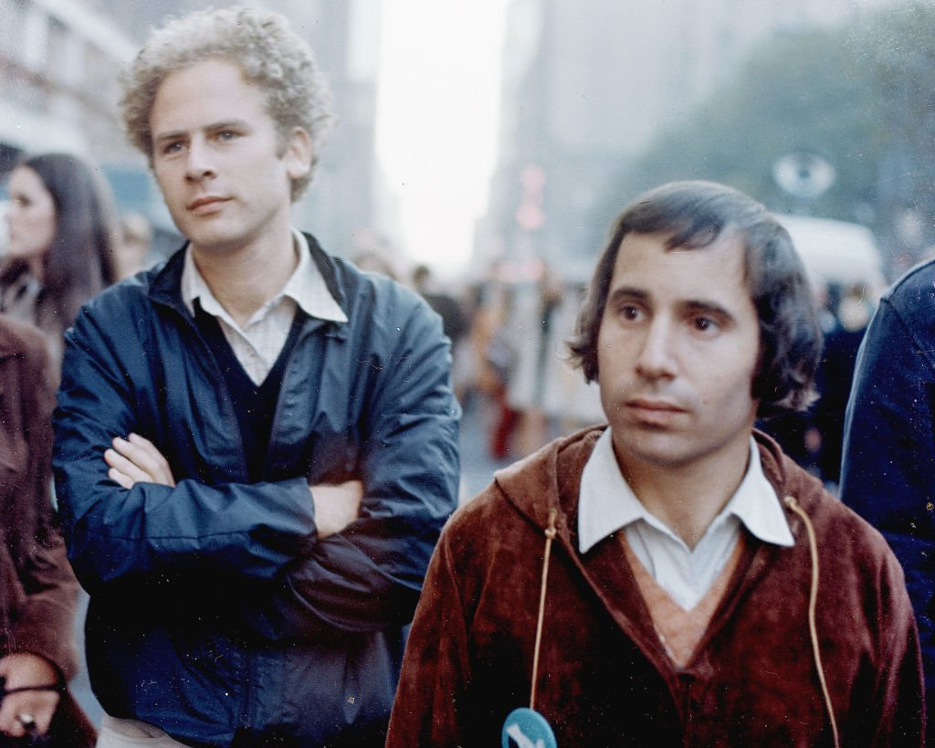 Art Garfunkel and Paul Simon stand on a street during the filming of a televison special called 'Songs of America,' which aired on November 30, 1969. | Photo: Getty Images