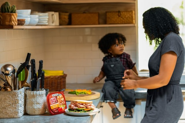 boy sitting on kitchen counter while his mother makes food   Source: Unsplash