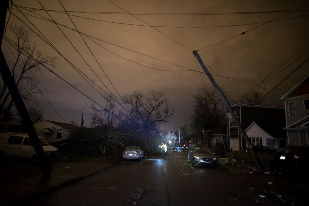 In the wake of a tornado, a Nashville resident shine a light on the debris and damage as she made her way down Underwood St. on March 3, 2020, in Nashville, Tennessee | Source: Brett Carlsen/Getty Images