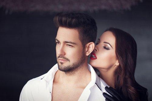 A woman whispering into a bearded man's ear. | Source: Shutterstock.