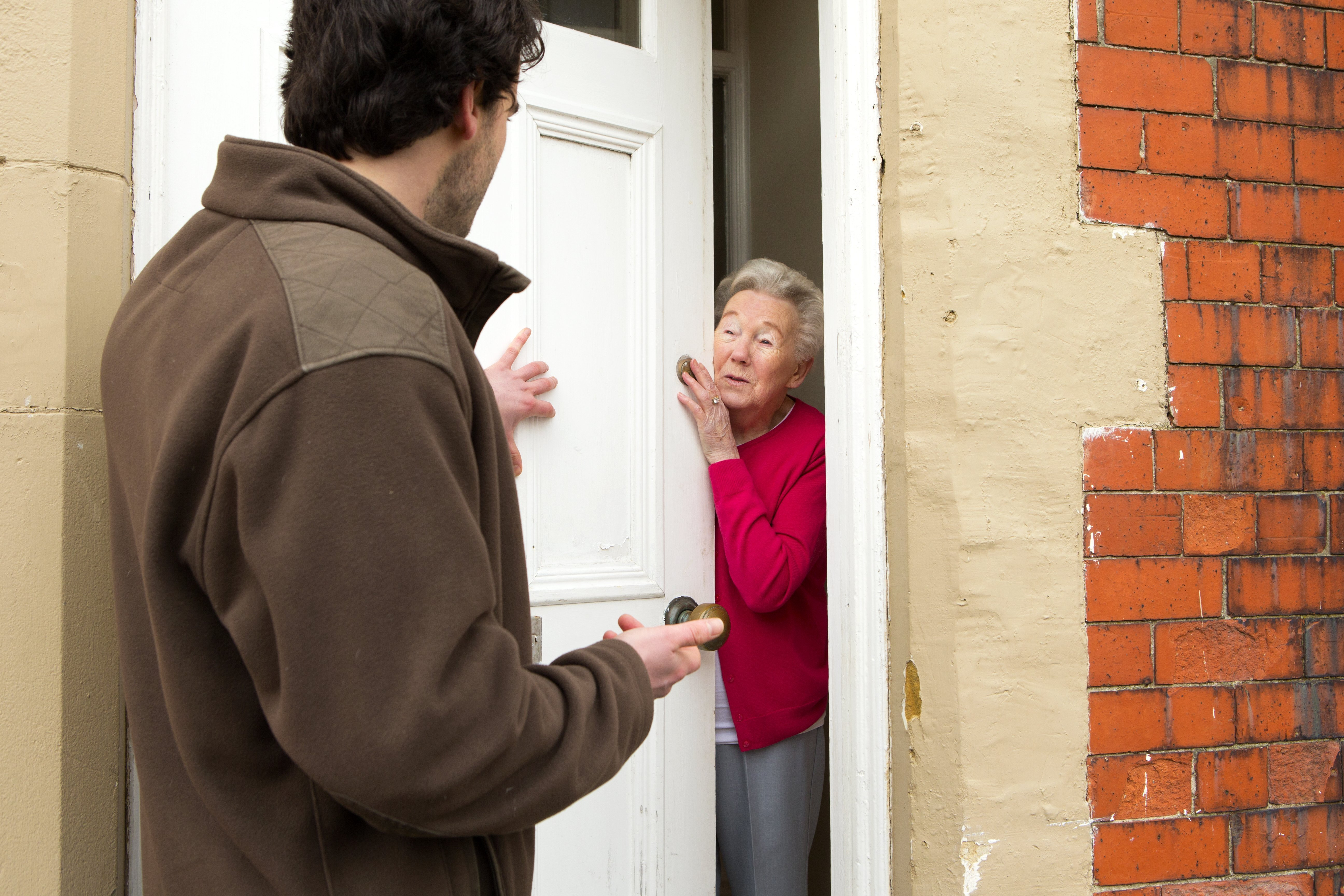 A horizontal image of a male door salesman putting an older lady under pressure to buy. | Photo: Getty Images