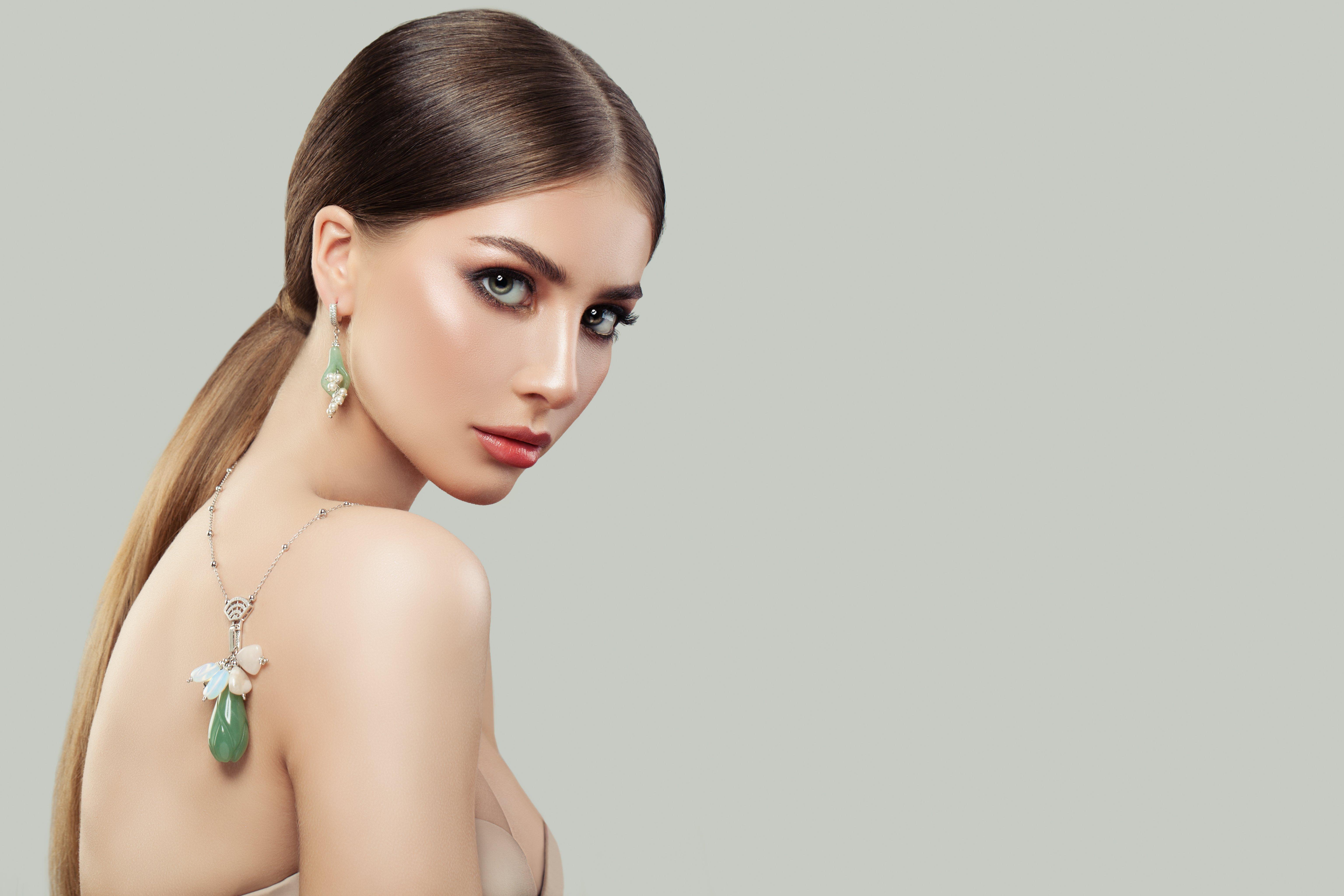 Retrato de mujer elegante luciendo un collar y pendientes con perlas. Fuente: Shutterstock
