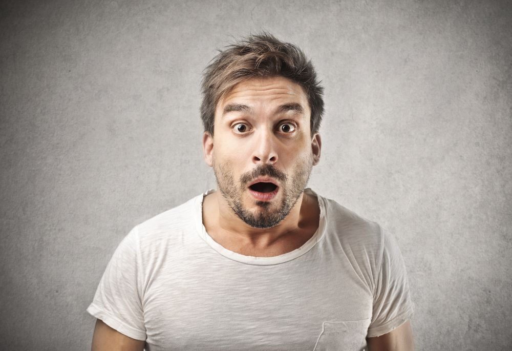 A guy looks shocked at the camera. | Source: Shutterstock